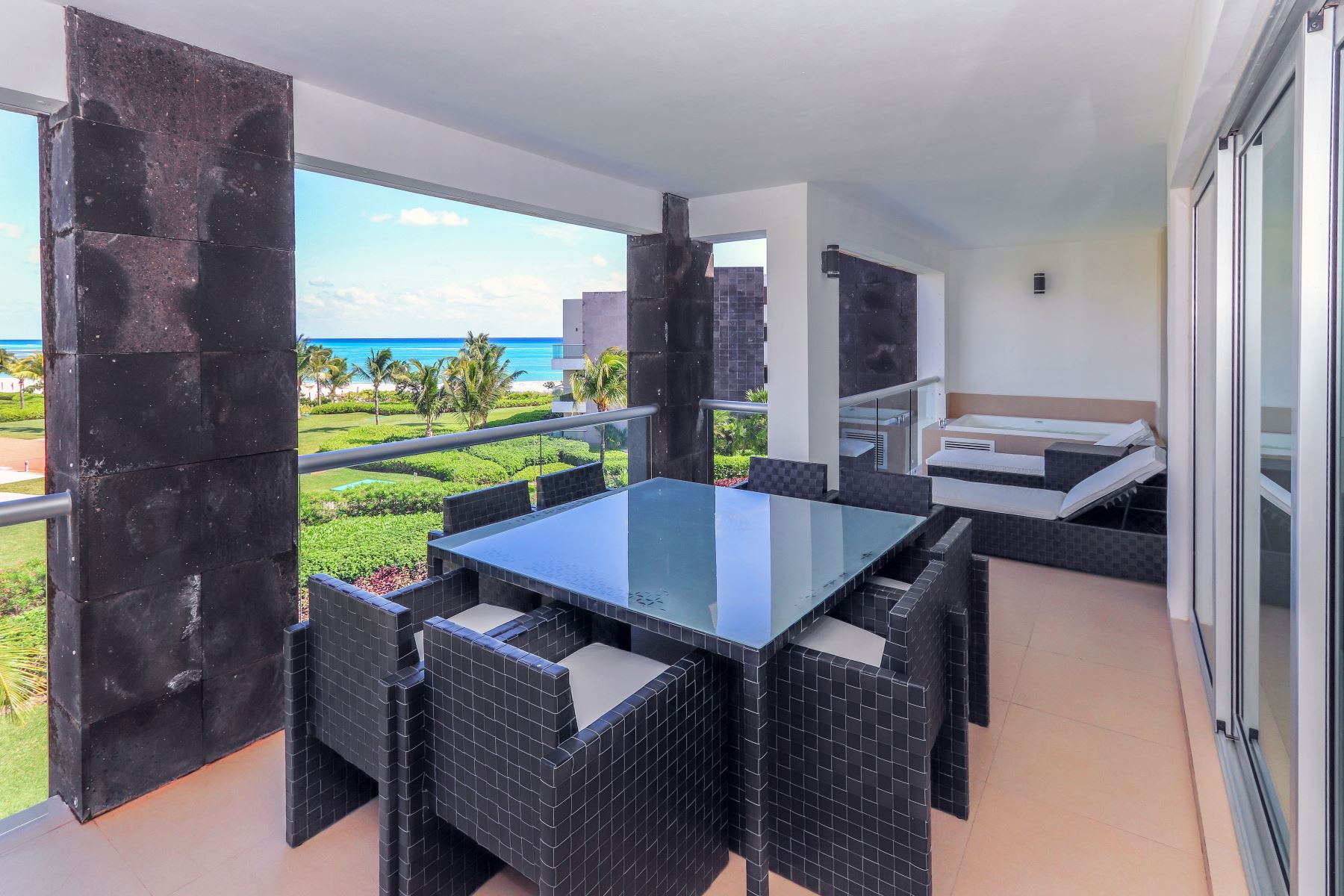 Ocean view terrace with Jacuzzi, lounge chairs, and patio table with seating for 8